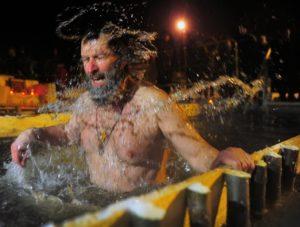 мужчина купается в проруби