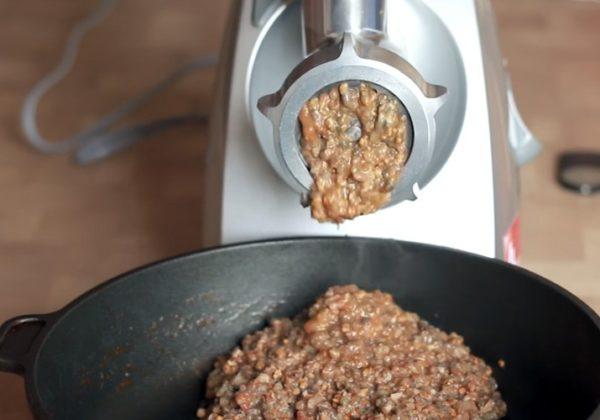 Содержимое сковороды измельчаем при помощи мясорубки